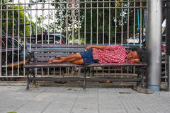 A homeless man sleeping on the bench beside the road in Bangkok T Stock Images