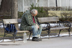 Homeless man sleeping on a bench Royalty Free Stock Photography