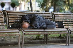 Homeless man sleeping on a bench. Sofia, Bulgaria - 8 August 2018: Homeless man in dark clothes sleeps on a bench in a park in the center of Sofia stock photography