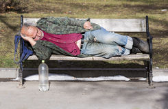 Homeless man sleeping on a bench Royalty Free Stock Image