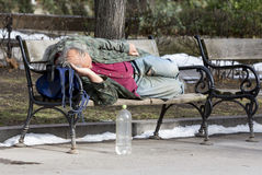 Homeless man sleeping on a bench Stock Images