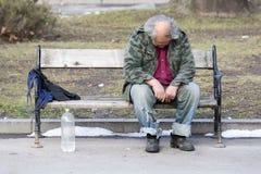 Homeless man sleeping on a bench Stock Image