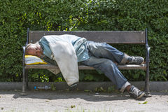 Homeless man sleeping on a bench Stock Photos