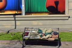 Homeless man sleeping on a bench in the street