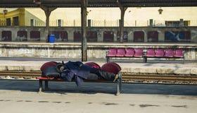 Homeless man sleeping in Bucharest North Railway Station stock photo
