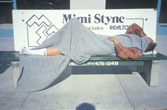 Homeless man sleeping at bus stop, Los Angeles, California Royalty Free Stock Photos