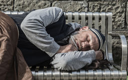 Homeless man sleeping with old blankets. On a park bench Stock Image