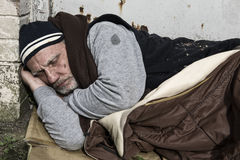 Homeless man sleeping in an old sleeping bag. Out on the streets Royalty Free Stock Image