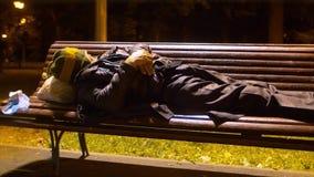 Homeless man sleeping on a park bench. A homeless man sleeping on a bench in a park stock video footage