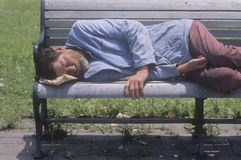Homeless man sleeping on a park bench, Los Angeles, California Stock Images