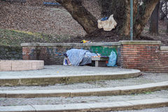 Homeless man sleeping peacefully on wooden bench Royalty Free Stock Photography