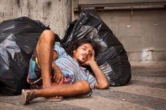 Homeless man sleeping on plastic bags Royalty Free Stock Image