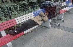 Homeless man sleeping on red, white and blue bench, New Jersey City Stock Photos