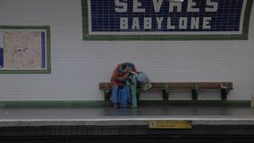 Homeless man sleeping at Sevres-Babylone subway station in Paris, France. Paris, France - September 29, 2017: Senior homeless man with bags is falling asleep at stock video footage