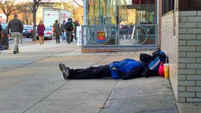 Homeless man sleeping on sidewalk royalty free stock photography