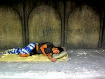 Homeless man sleeping on a sidewalk Stock Images