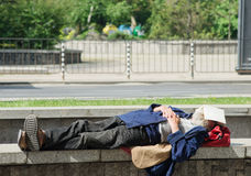 Homeless man sleeping on the street Stock Photography