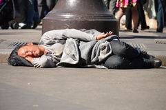 Homeless man sleeping on the street in Paris Stock Images