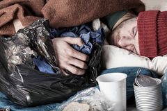Homeless man sleeping on the street Stock Images