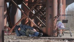 Homeless man sleeping under the bridge. Homeless man sleeping on the ground under the bridge in cold autumn weather, covering himself with jacket. Cart with bin stock footage