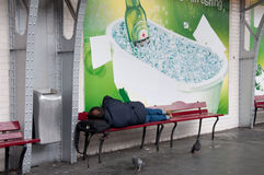 Homeless Man Sleeping Under Metro Ad Stock Photography