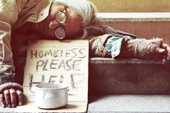 Homeless man sleeping on walkway street in the capital city. Could you please help homeless man sleeping on walkway street in the capital city royalty free stock photography