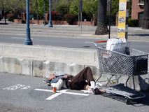 Homeless man sleeps on along the Embarcadero Stock Photo