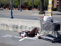 Homeless man sleeps on along the Embarcadero Stock Photo