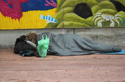 Homeless man sleeps in Barcelona. A poor beggar lying on the side of a street in the dirt in Cape Town royalty free stock image