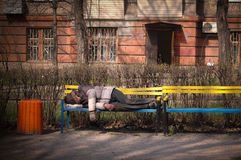 Homeless man sleeps on a bench Royalty Free Stock Images