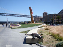 Homeless man sleeps on concrete slab near art Royalty Free Stock Photo