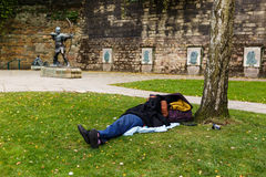 Homeless man sleeps rough near Robin Hood statue, Nottingham. Stock Photos