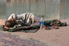 Homeless man sleeps on the sidewalk near the River Ganges in Haridwar, India. Stock Photo