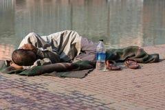 Homeless man sleeps on the sidewalk near the River Ganges in Haridwar, India. stock photo