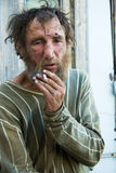 Homeless man smoking cigarette Stock Photo
