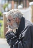 A homeless man smoking. Stock Images