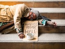 Homeless man on stairs begging for money. A homeless man sleeping on a stairway with a sign asking for money Stock Photos