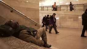 Homeless man on stairs in Grand Central Station, NY with people walking by stock footage