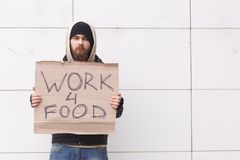 A homeless man stands near a wall in cold weather with a sign about the request for work for food. Outdoor. A homeless young man with a beard and in a hood Stock Photo