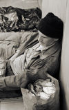 Homeless Man on the Street. Sepia toned photo of a homeless man on the street, seated, surrounded by his meager belongings royalty free stock photos