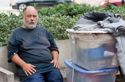 Homeless man on streets. Poor homeless man on bench with possessions Stock Image