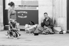 Homeless man talking to a woman passerby Royalty Free Stock Photos