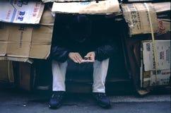 Homeless Man in Tokyo. A homeless man living inside a cardboard shelter along the streets of Tokyo near Shinjuku Station grooms his fingernails