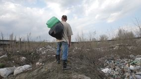 Homeless man standing on garbage hill at dump site. Homeless man with trash bin bags on his shoulder standing on the hill at garbage dump site in city. Slow stock video footage
