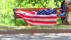 Homeless man using USA flag as a blanket. Old man with no money and home living in the streets stock footage