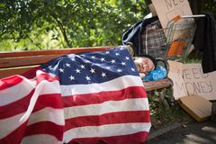 Homeless man using USA flag as a blanket. Royalty Free Stock Image