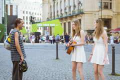 A homeless man watches as two girls-twins sing and play guitar Royalty Free Stock Photography