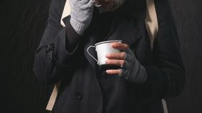 Homeless Mature bearded man stands in the rain holding a Cup to collect money.