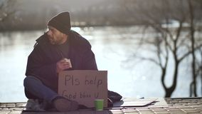 Homeless man eating sandwich and begging for help stock video