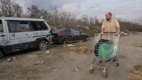 Homeless mature man pushing cart at garbage dump. Front view of mature homeless man in dirty t-shirt walking at garbage dump site with abandoned old cars stock video footage